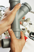 Plumbing fittings in his hand — Stock Photo