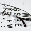 Glasses on eyesight test chart — Stock Photo #8773744