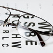 Glasses on eyesight test chart - Stock Photo