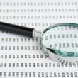 Magnifying glass and document with figures — Stock Photo
