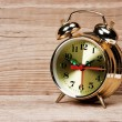 Golden alarm clock on wooden table — Stock Photo