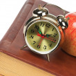 Golden alarm clock and apple on the book isolated — Stock Photo #8869860