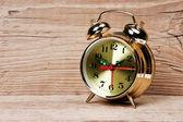 Golden alarm clock on wooden table — Stock Photo