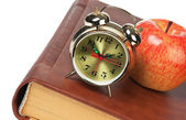 Golden alarm clock and apple on the book isolated — Stock Photo