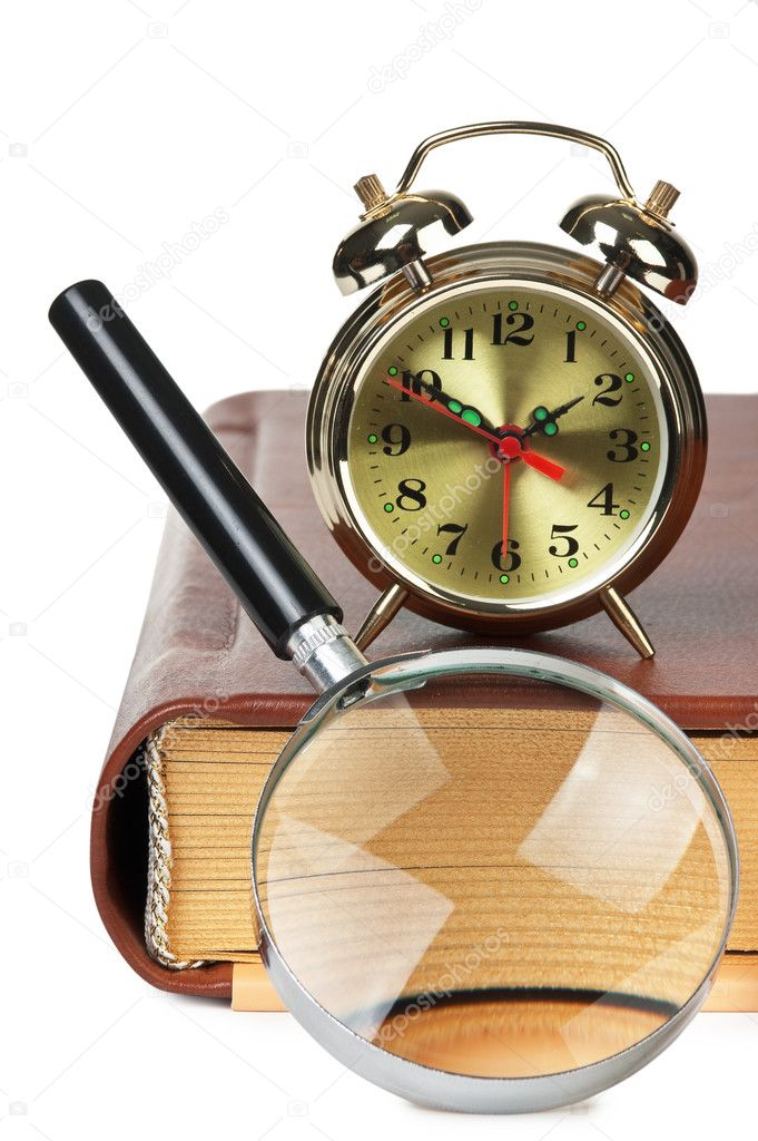 Golden alarm clock and magnifying  glass on the book isolated on a white background  Stock Photo #8869838