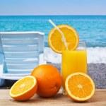 Glass of orange juice on a beach — Stock Photo