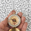 Compass in hand on the background of the labyrinth — Stock Photo