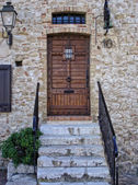 Wooden front door in the ancient stone house — Stok fotoğraf