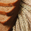 Slices of rye bread and ears of corn on a wooden table — Stockfoto