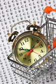 Alarm clock in a shopping basket — Stockfoto