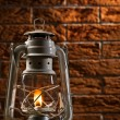 Kerosene lamp on brick background — Stock Photo