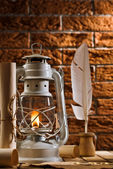 Composition of old writing items and kerosene lamp — Stock Photo