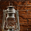 White kerosene lamp on background of the brickwall — Stock Photo