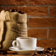 Cup and bag with beans of coffee - Stock Photo