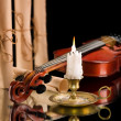 Old violin witn candle ond old scroll of paper — Stock Photo