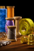 Sewing items on brown wooden bards — Stock Photo