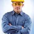 Stock Photo: Worker in a hardhat and yellow goggles