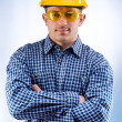 Foto Stock: Worker in a hardhat and yellow goggles