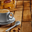Close-up coffee cup and grinder on wooden table — Stock Photo