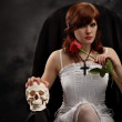 Young sexy witch with a skull and rose — Stock Photo