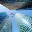 Airliner flying over skyscrapers — Stock Photo