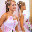 Beautiful bride in a pink dress near the mirror — Stock Photo