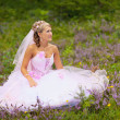 Beautiful bride is sitting in the forest — Stock Photo