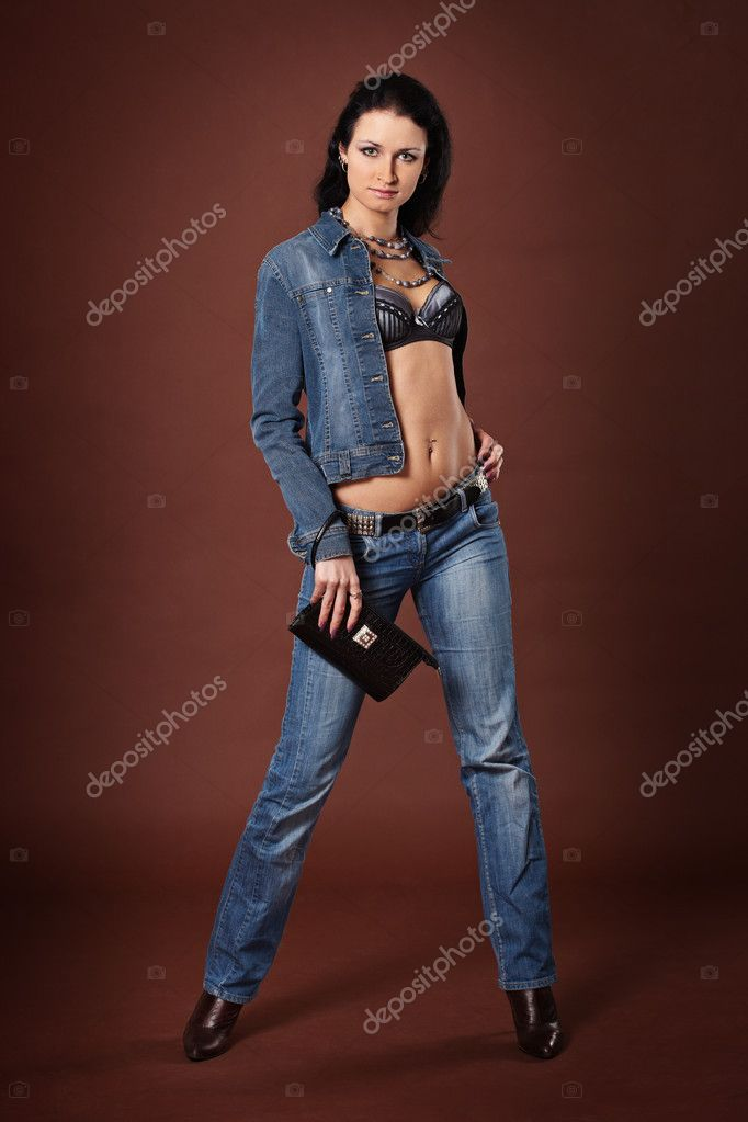 Beautiful fashionable girl in jeans on a brown background — Stock Photo #9134117