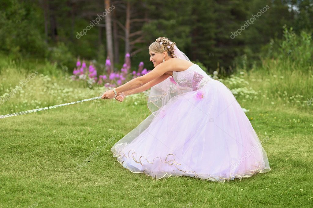 Funny bride pulls the chain - outdoors scene — Stock Photo #9134470