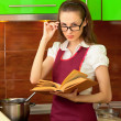 Girl reading a cookbook on kitchen — Stock Photo