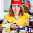 Smiling cashier girl in red and yellow uniform — Stock Photo