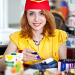 Smiling cashier girl in red and yellow uniform - Stock Photo
