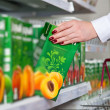 Woman hand take box of juice in grocery store - Stok fotoğraf