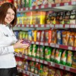 Pretty woman buyer in grocery shop at shelves with products — Stok fotoğraf