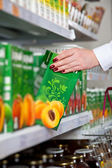 Woman hand take box of juice in grocery store — Stock Photo