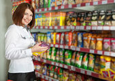 Pretty woman buyer in grocery shop at shelves with products — Стоковое фото