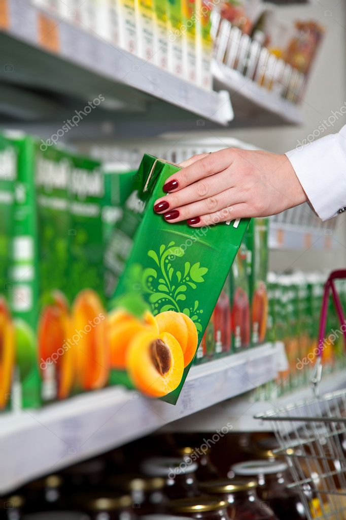 Woman hand take box of juice in supermarket — Zdjęcie stockowe #10632084