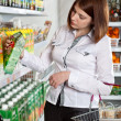Woman in a supermarket choosing box of juice — Stock Photo