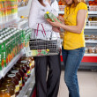 Two woman in supermarket choosing juice — Stock Photo