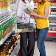 Two woman in supermarket choosing juice — Stock Photo #10647394