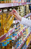 Womens hand selects the bottle of oil at the store — Stock Photo