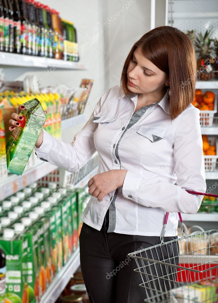 Woman in a supermarket choosing box of juice  Stock Photo #10647158