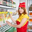 Female the seller in the supermarket holding a box of juice - Stock Photo