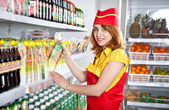 Female the seller in the supermarket holding a box of juice — Stock Photo