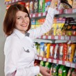 Pretty woman buyer in grocery shop at shelves with products — Stock Photo
