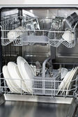 Dishwasher with white plates and steel cutlery — Stock Photo