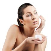 Retrato de jovem aplicar creme hidratante no rosto bonito — Foto Stock