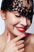 Beautiful woman with red lips and lace mask over her eyes. — Stock Photo
