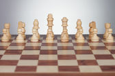Chess board with figures over grey — Stock Photo