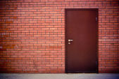 Red brick wall and the iron closed door — Stock Photo